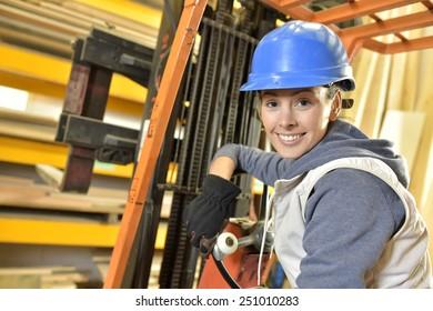 Factory operator in warehouse using storage vehicle