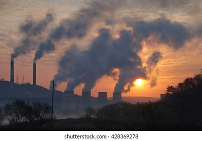 Factory pipe polluting air against sunset, environmental problems, smoke from chimneys