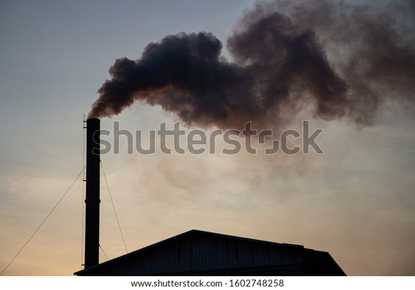 Factory pipe polluting air against sunset, environmental problems