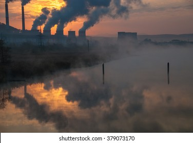 Factory pipe polluting air, smoke from chimneys reflect in river water against sunset, environmental problems, ecology theme