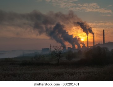 Factory pipe polluting air, smoke fron chimneys against sunset, environmental problems