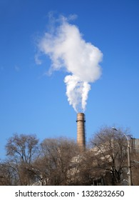 Factory pipes with thick white smoke polluting environment in blue sky background
