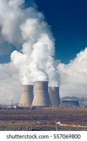 Factory pipes with thick white smoke from heat energy nuclear plant polluting environment