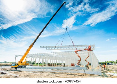 Factory production hall and warehouse under construction with crane, steel frame with parts