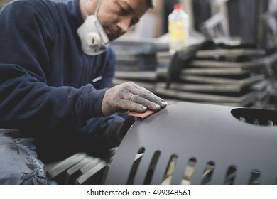 Factory for production heavy pellet stoves and boilers. Worker sandblasting parts of stoves. Selective focus on worker's hand.