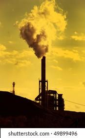 Factory smoke stack emitting toxic fumes in yellow green atmosphere