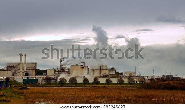 Factory smoke stack and pipes puff into air. Atmospheric air pollution industrial scene. Non-ecological and non-sustainable manufacturing.