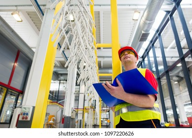 Factory supervisor in yellow reflective west with red helmet. Factory engineer checking production line holding blue folder with documents