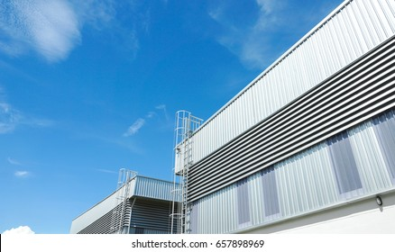 Factory warehouse and industrial concept - Wall and roof of Factory or warehouse building in industrial estate with blue sky and copy space