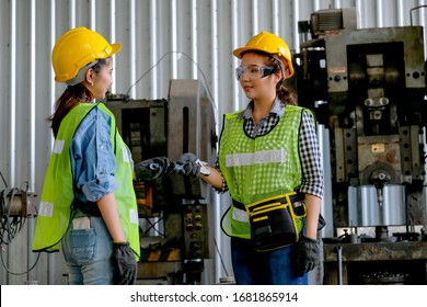 Factory woman technician or engineer worker give wrench to her co-worker in front of machine with day light assign by manager. Concept of good system and manager support  better industrial business.