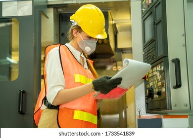 Factory woman wearing hygienic mask to Protect Against Covid-19 working and checking machine in factory on the machine,Coronavirus  pandemic in people affect industrial business.