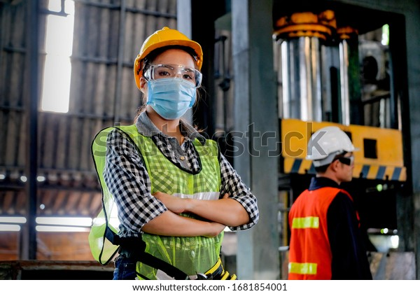 Factory woman worker or technician with hygienic mask stand with confident action with her co-worker engineer in workplace during concern about covid pandemic in people affect industrial business.