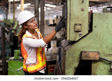Factory woman worker at work in the industry factory, work with CNC machine. Factory female worker maintaining machine in the industrial factory