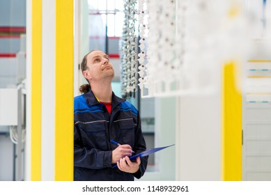 Factory worker checking products on production line. Worker taking notes during quality control of products