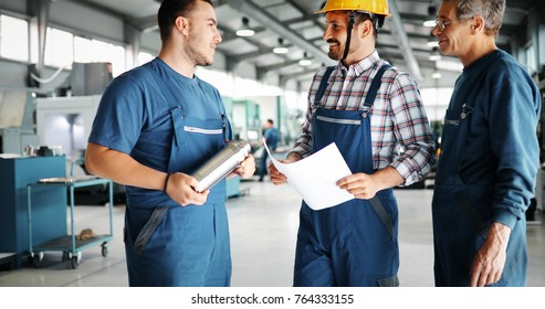Factory worker discussing data with supervisor in metal factory