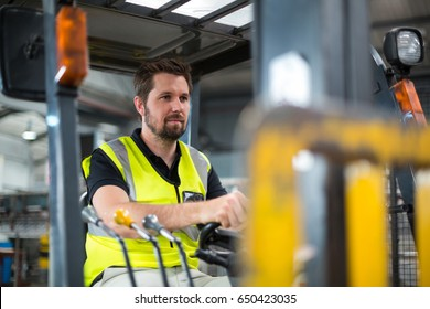 Factory worker driving forklift inn factory