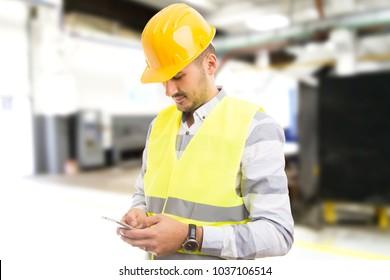 Factory worker employee chatting browsing texting on smartphone during working hours being distracted from work