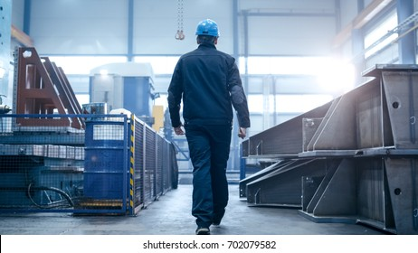 Factory worker in a hard hat is walking through industrial facilities.