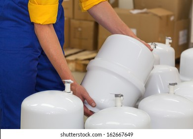 Factory worker holding a pressure vessel ready to be sold