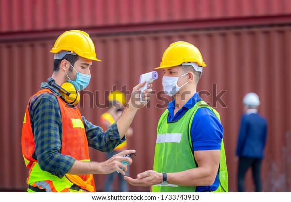 Factory worker man checking fever by digital thermometer for scan and protect from Coronavirus (COVID-19) at cargo containers - Healthcare Concept