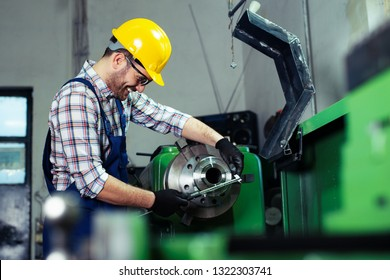 Factory worker measure detail with digital caliper micrometer during finishing metal working on lathe machine