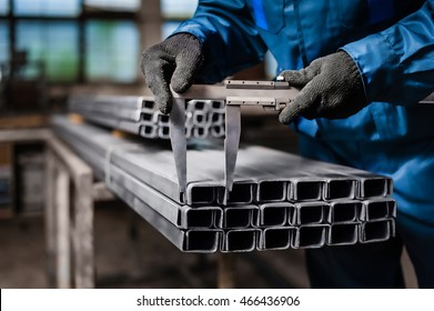 Factory worker measures the metal profile