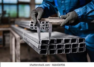 Factory worker measures the metal profile - Shutterstock ID 466436906