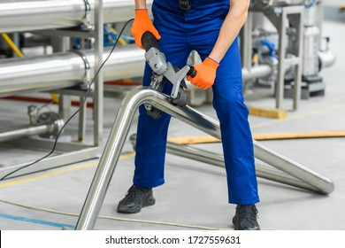 Factory worker operate with stainless steel pipe sander polishing machines. Remove spot welds or eliminate deep scratches. Grind and polish up to high-gloss finish.