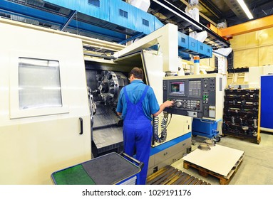 factory worker operates a cnc milling machine for the production of mechanical components