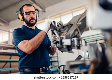 Factory worker operating band saw cutting machine for steel bars in the industrial factory