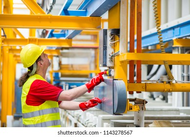 Factory worker pressing a red button. Factory worker starting a machine