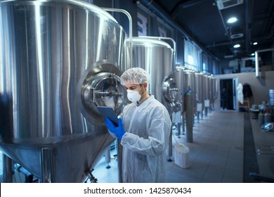 Factory worker technologist in protective uniform with hairnet and mask controlling food production on tablet computer.