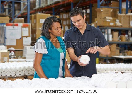 Factory Worker Training Colleague On Production Line