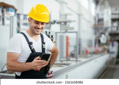 Factory worker using phone. Factory worker talking to smart phone.