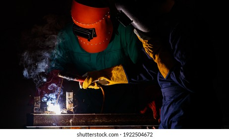A factory worker wearing a green mechanic coveralls and safety helmet welding metalwork at night time in a factory while his colleague looking at a spark from welding.