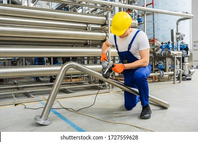 Factory worker in yellow hard hat operate with stainless steel pipe sander polishing machines. Remove spot welds or eliminate deep scratches. Grind and polish up to high-gloss finish. Indoor.