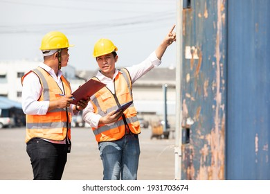factory workers or engineers talking and exploring container in factory workshop