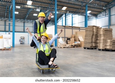 factory workers moving cart and funny pose in warehouse storage