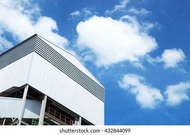 Factory/warehouse with beautiful cloud sky background. Focus on factory.