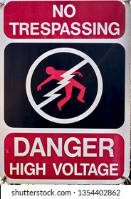 Faded Danger High Voltage sign with No Trespassing and person being electrocuted