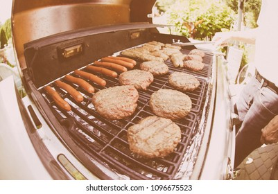 Faded Film Look shot of Grilling Burgers and Dogs on a gas grill on a sunny day in the summer