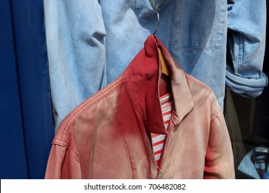 Faded red Breton jacket with collar turned up, hanging from faded blue jacket