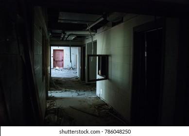 Faded red door at end of dark hallway in abandoned high school