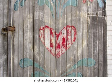 Faded red heart with chipped paint on old grey wooden door with lock.