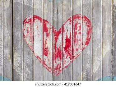 Faded red heart with chipped paint on old grey wooden door.