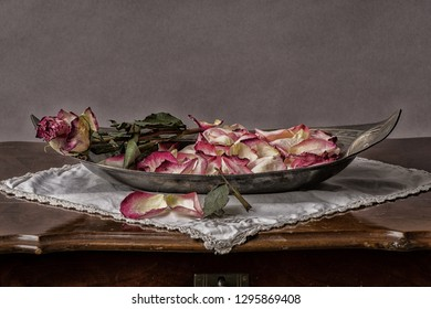 faded roses in a bowl on the side table in vintage mood