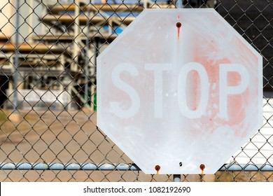 A faded stop sign on a chain link fence. Little red is left on the sign. An industrial site is visible in the background.