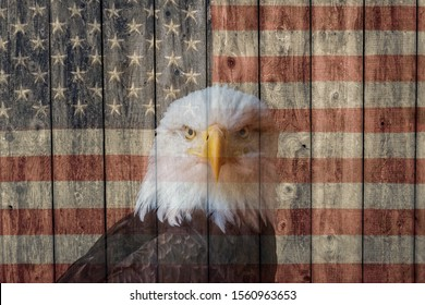 faded vintage american flag and bald eagle painted on the weathered wood  side of a barn