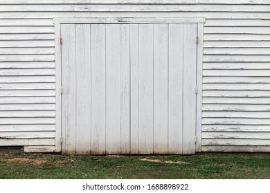 a faded white wooden warehouse building doorway and grass