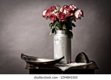fading bouquet of flowers, in old milk can on old side table in vintage mood